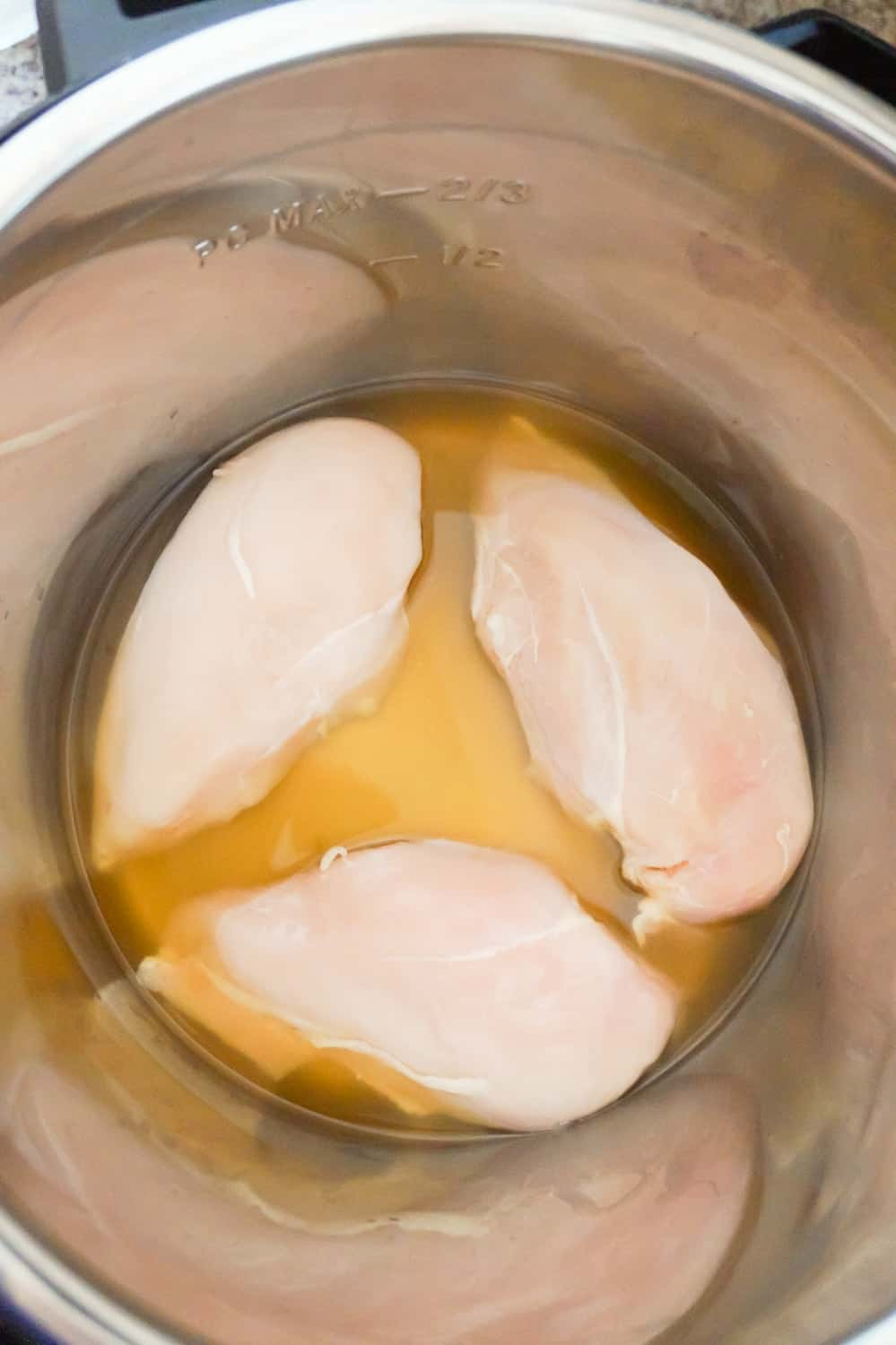 raw chicken breasts in broth in an Instant Pot