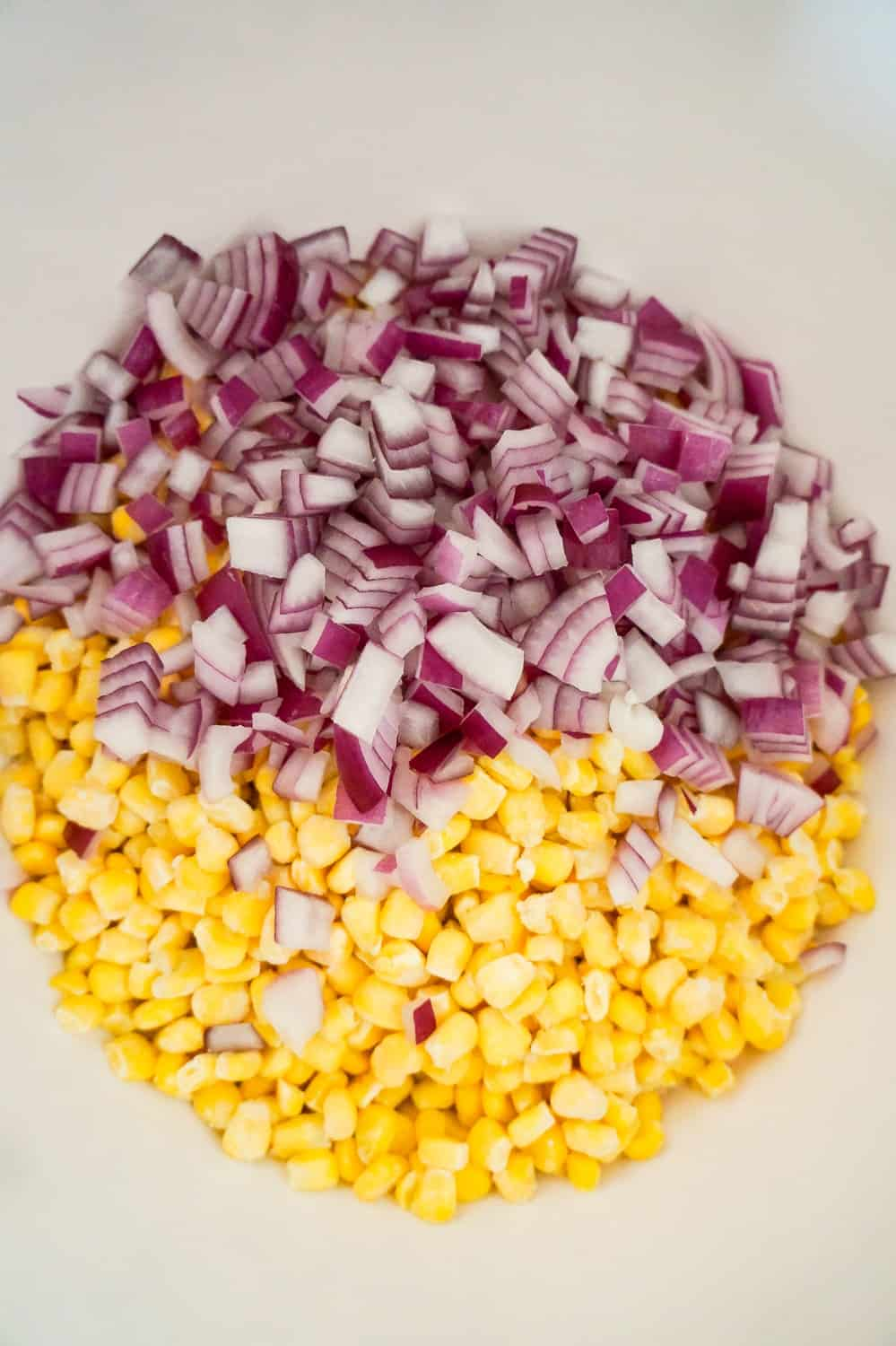 diced red onions and frozen corn in a mixing bowl