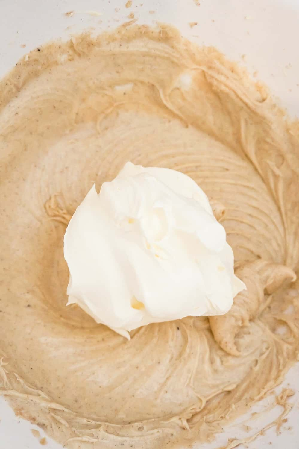 Cool Whip on top of pumpkin spice cheesecake filling in a mixing bowl