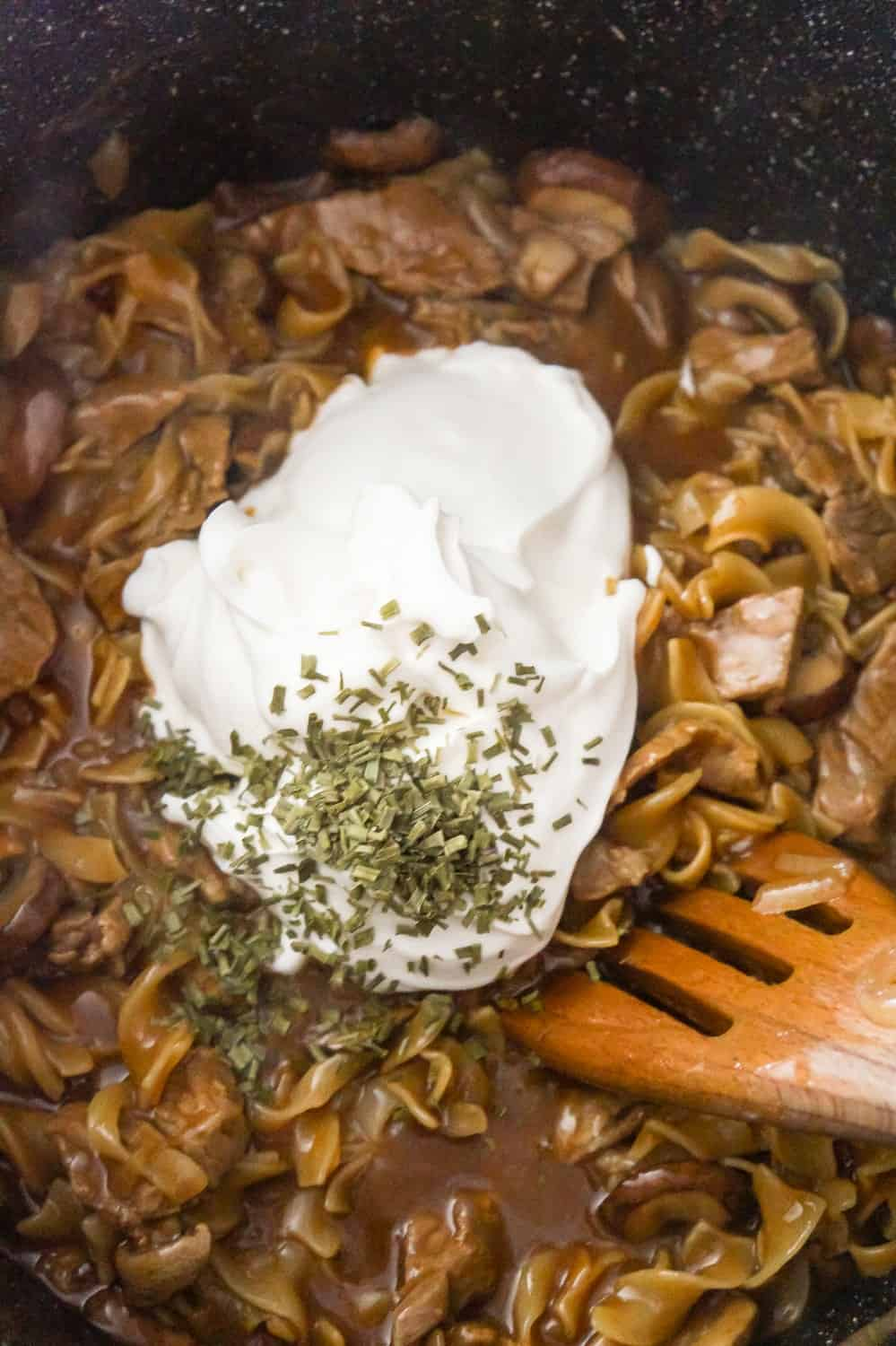 sour cream and dried chives on top of steak and noodles in a large pan