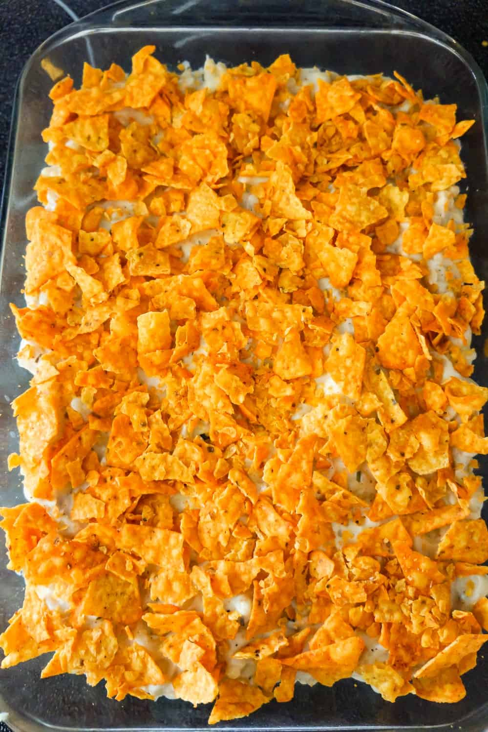 crumbled Doritos on top of mac and cheese in a baking dish