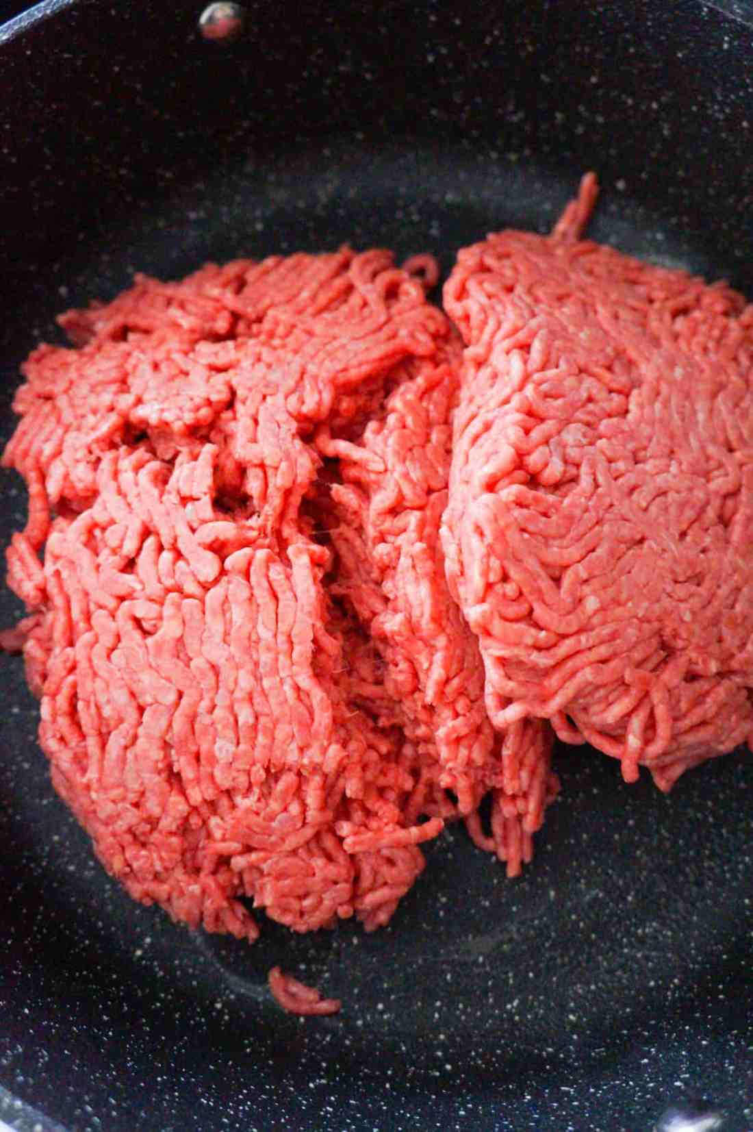 raw ground beef in a saute pan