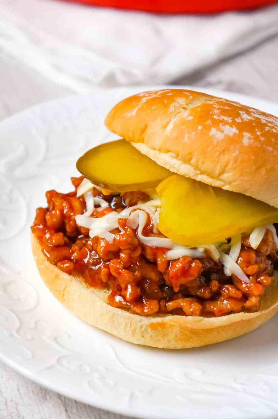Honey BBQ Chicken Sloppy Joes are an easy weeknight dinner recipe using ground chicken, tossed in honey and BBQ sauce and topped with mozzarella cheese and dill pickles.