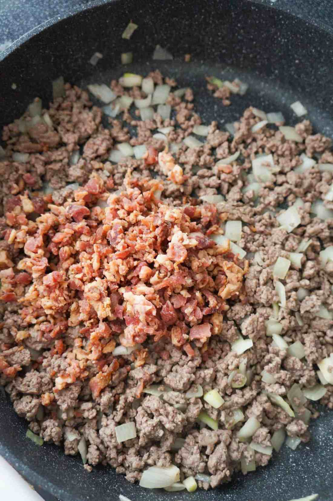 crumbled bacon on top of cooked ground beef and onions in a pan