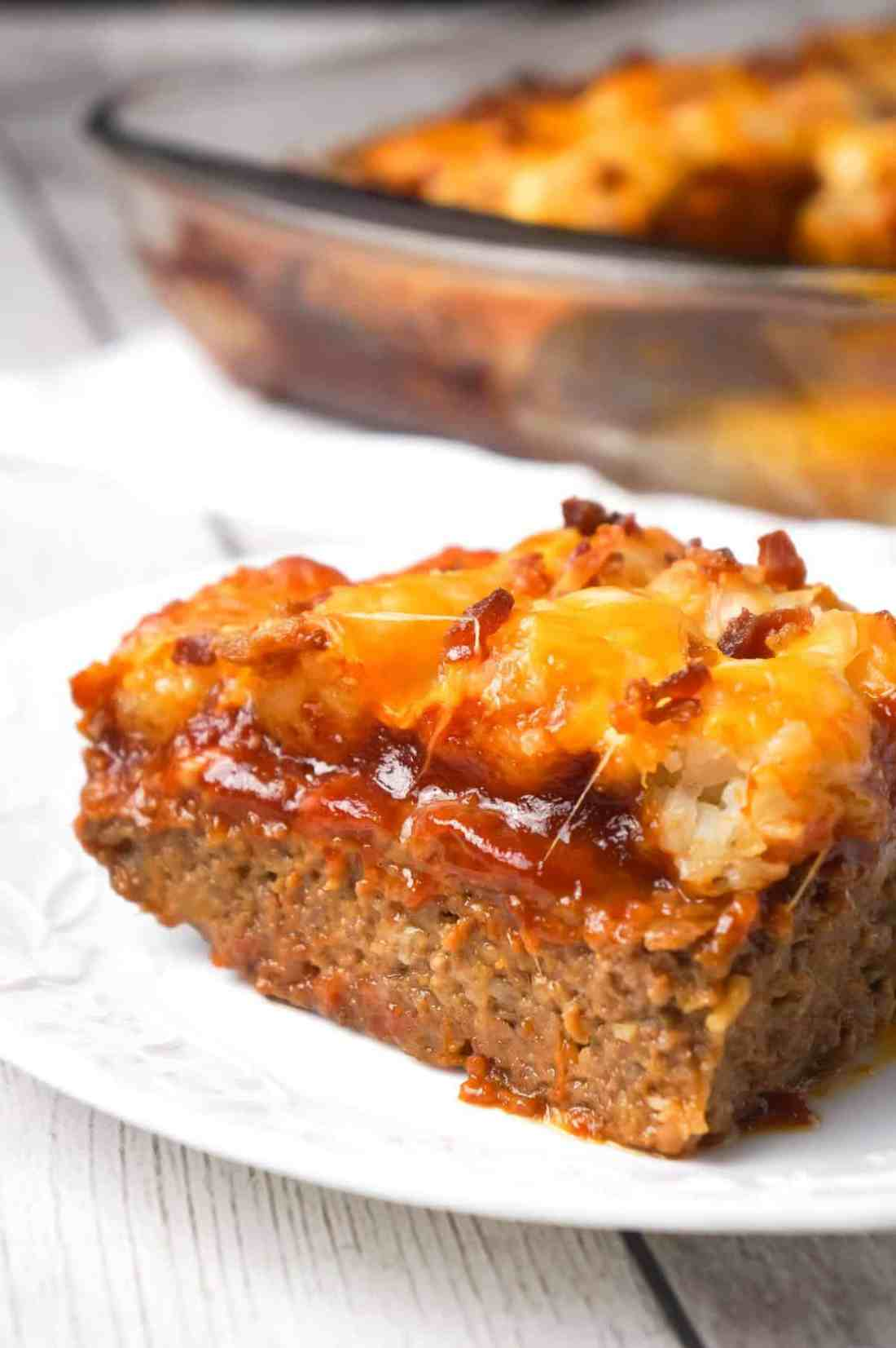 Cheesy Tater Tot Meatloaf Casserole is an easy ground beef dinner recipe with a meatloaf base, topped with a ketchup and bbq sauce glaze, tater tots, shredded cheese and crumbled bacon.