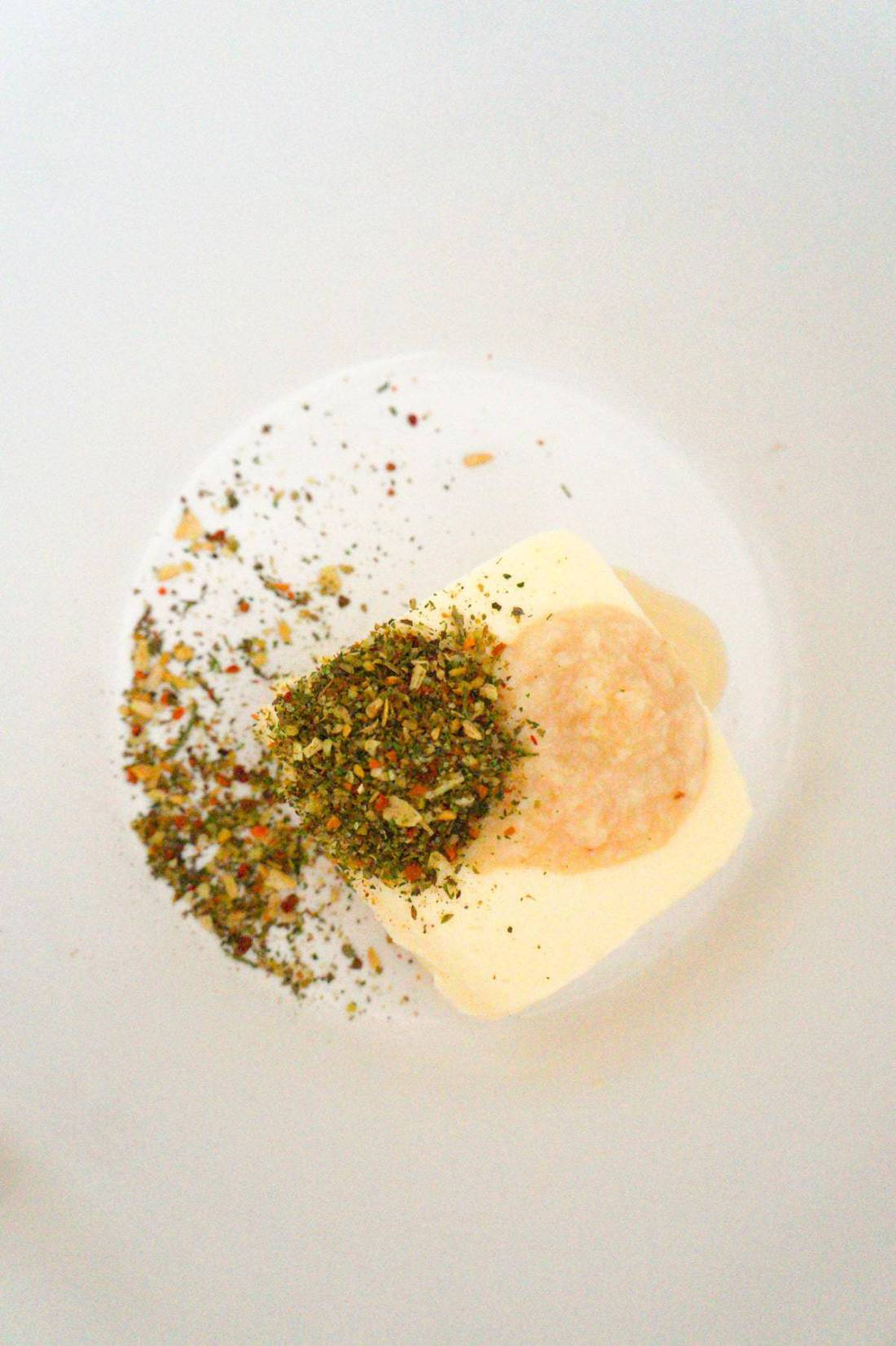 softened butter, Italian seasoning and garlic puree in a mixing bowl