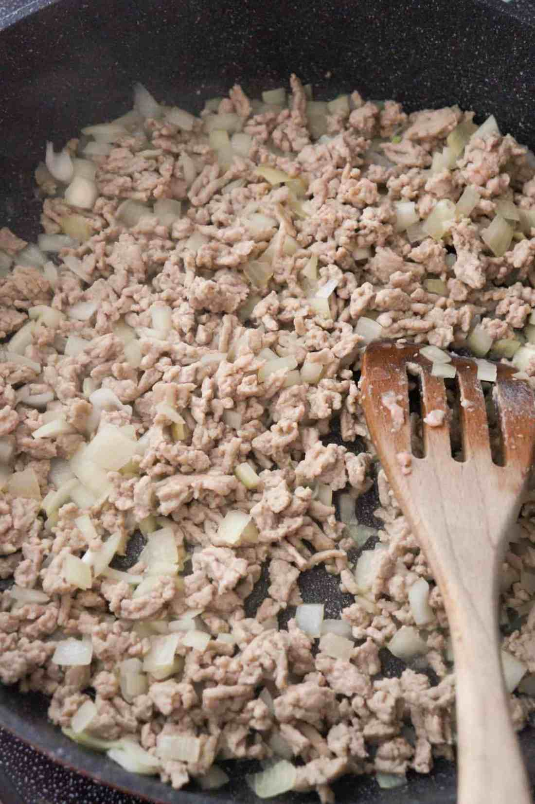 cooked ground chicken and diced onions in a saute pan
