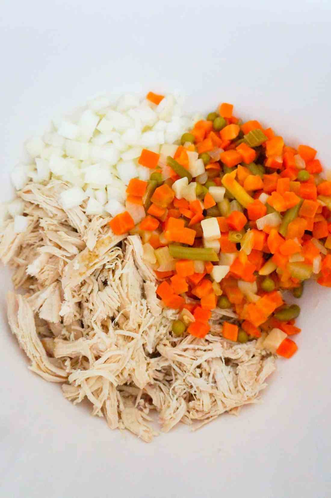 shredded chicken, diced onions and mixed veggies in a mixing bowl