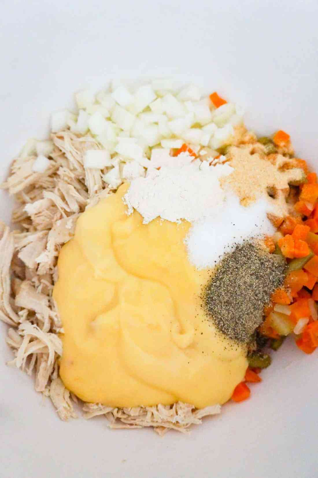 cream of chicken soup and spices on top of shredded chicken and veggies in a mixing bowl
