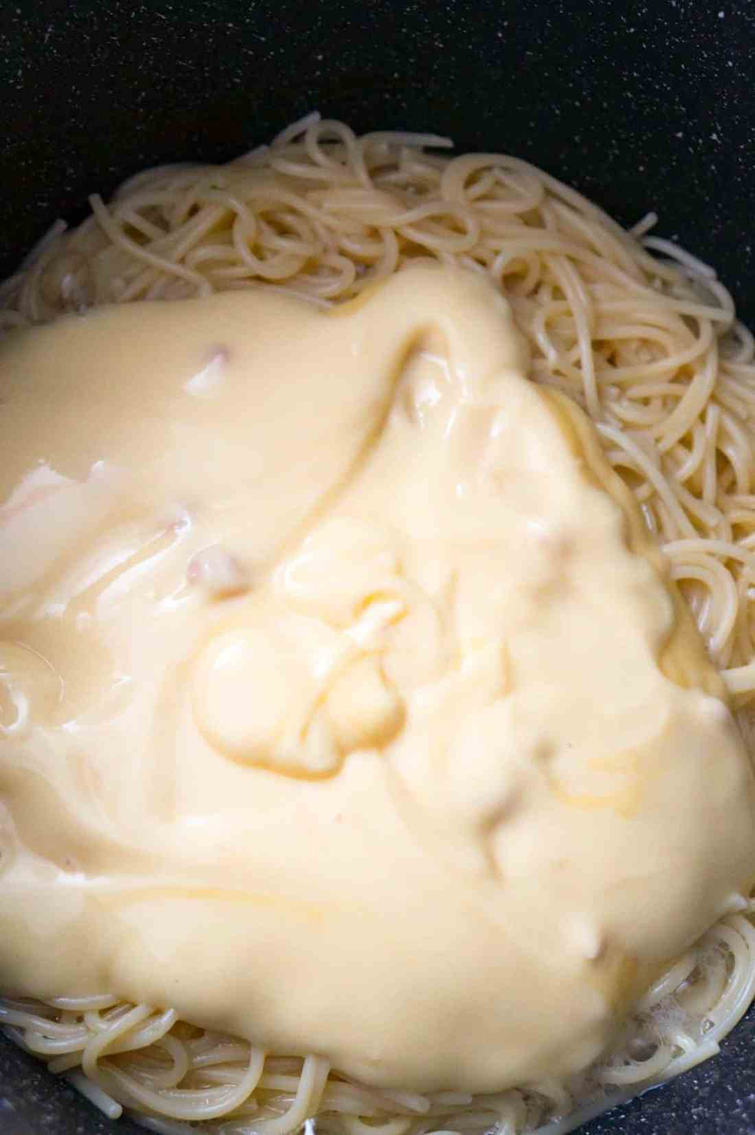 condensed cream of chicken soup on top of spaghetti in a pot