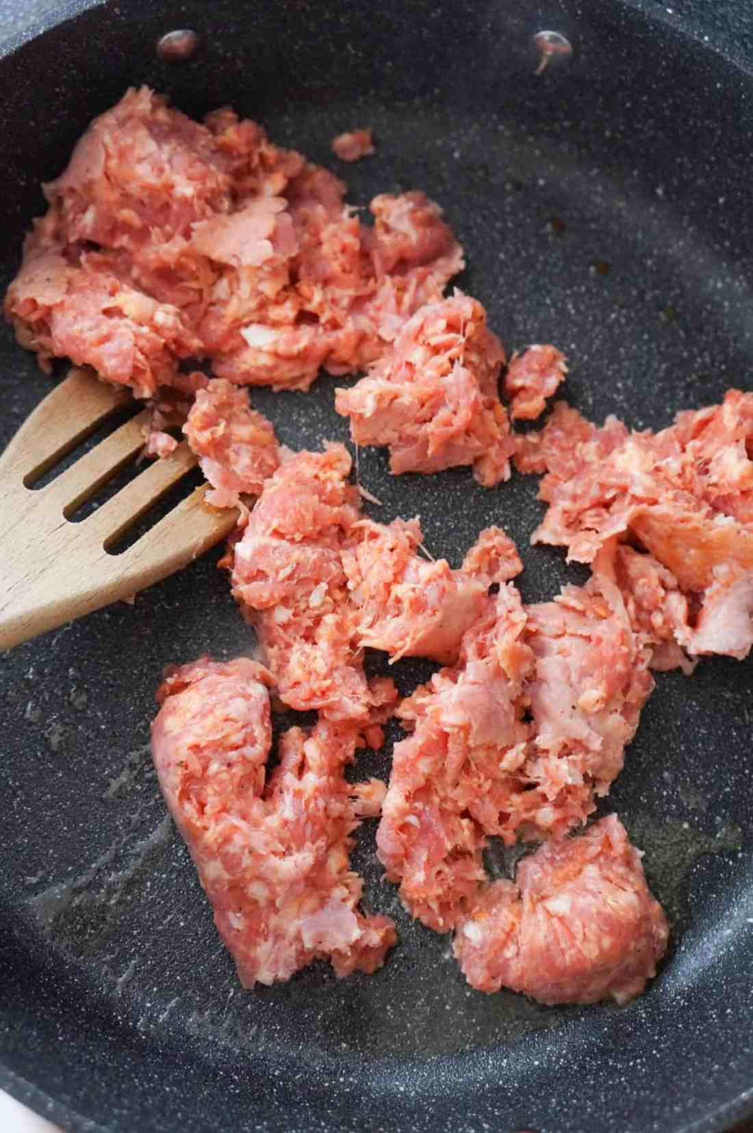 raw Italian sausage meat in a saute pan