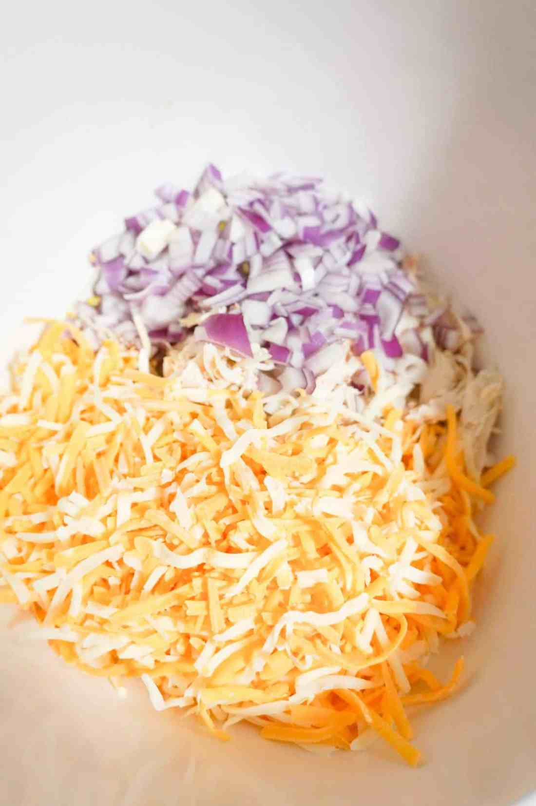 shredded cheese, diced red onion and shredded chicken in a mixing bowl
