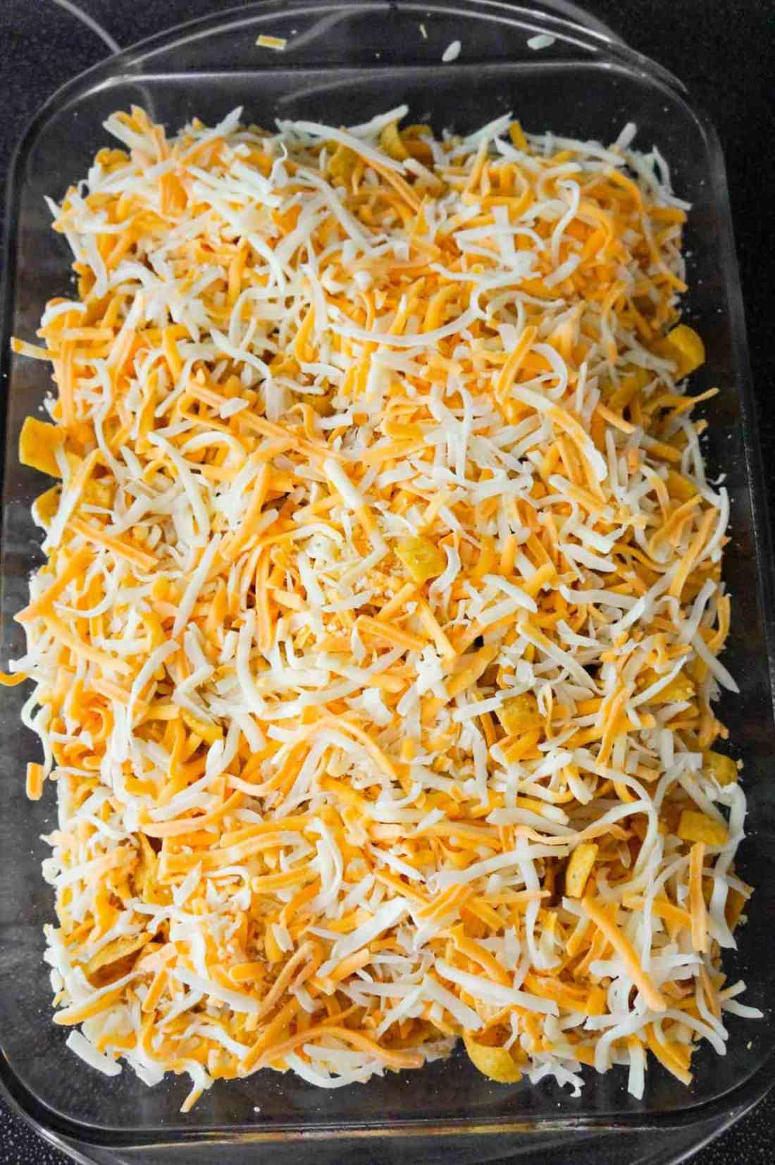 shredded mozzarella and cheddar cheese on top of buffalo chicken frito pie