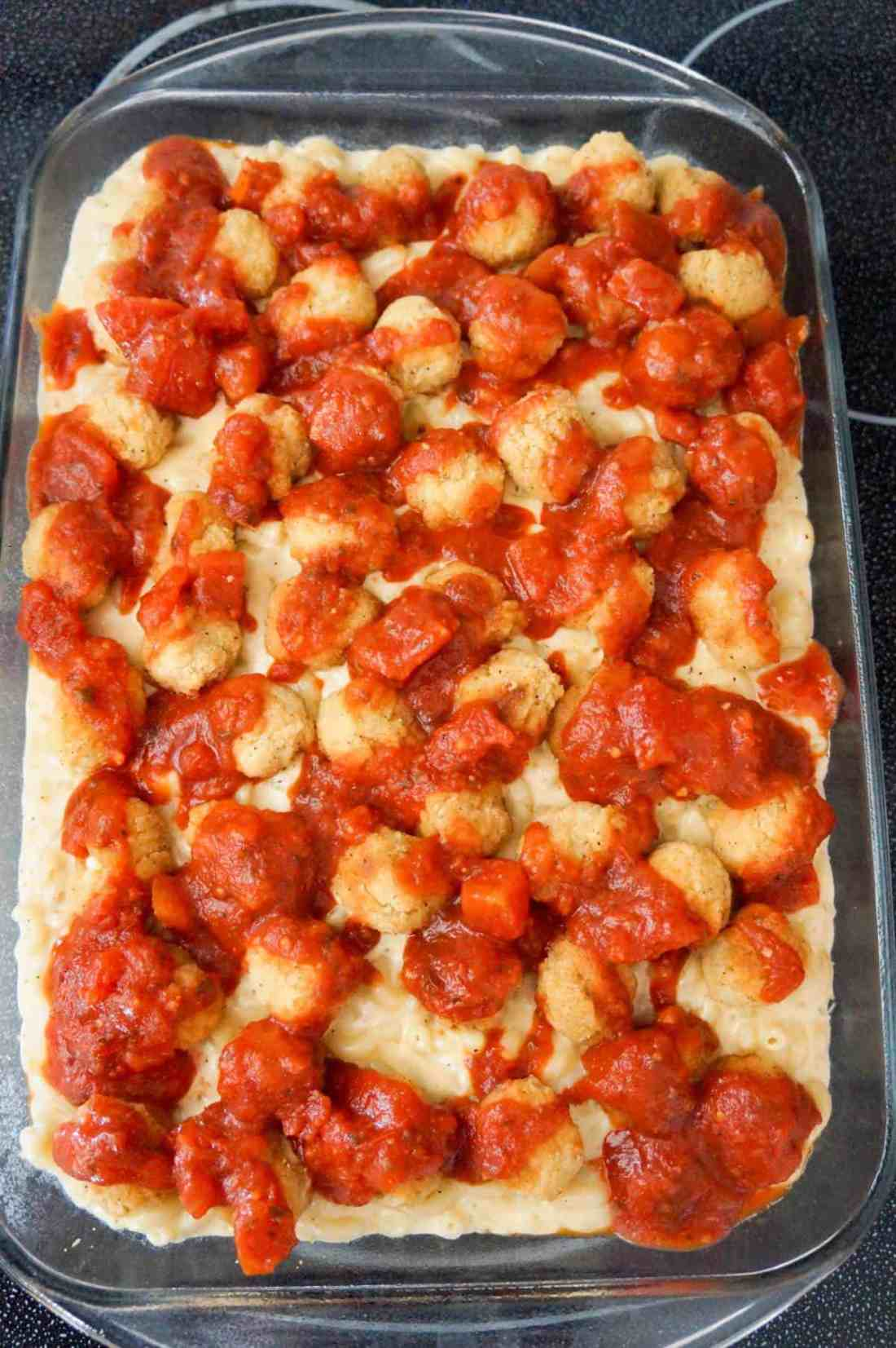 marinara sauce and popcorn chicken on top of mac and cheese in a baking dish