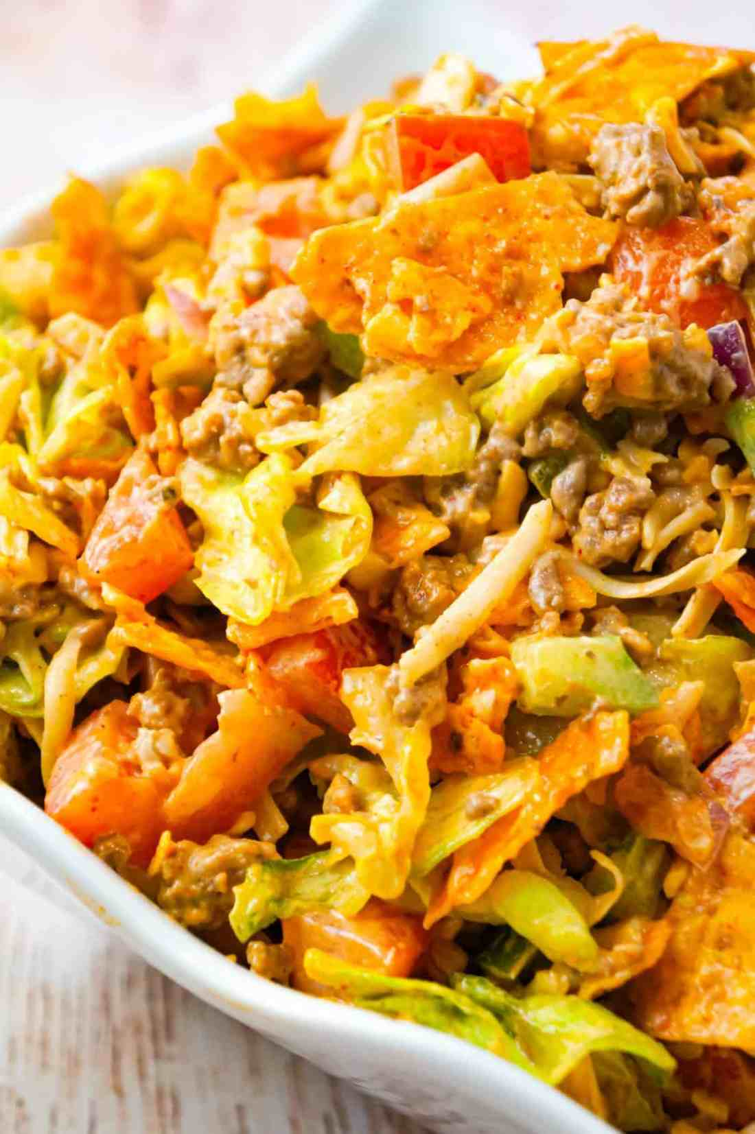 Doritos Taco Salad is a delicious salad loaded with iceberg lettuce, red onions, green peppers, tomatoes, shredded cheese, ground beef and crumbled Doritos all tossed in salsa and ranch dressing.