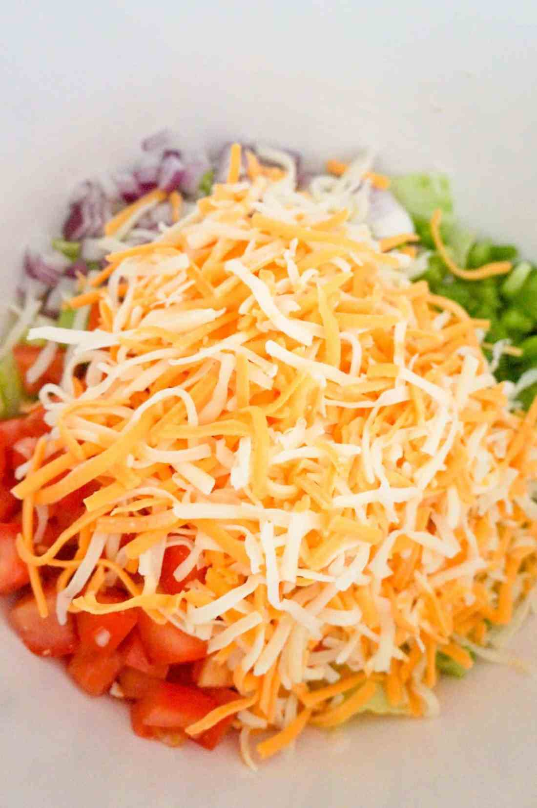 shredded cheese on top of salad in a mixing bowl