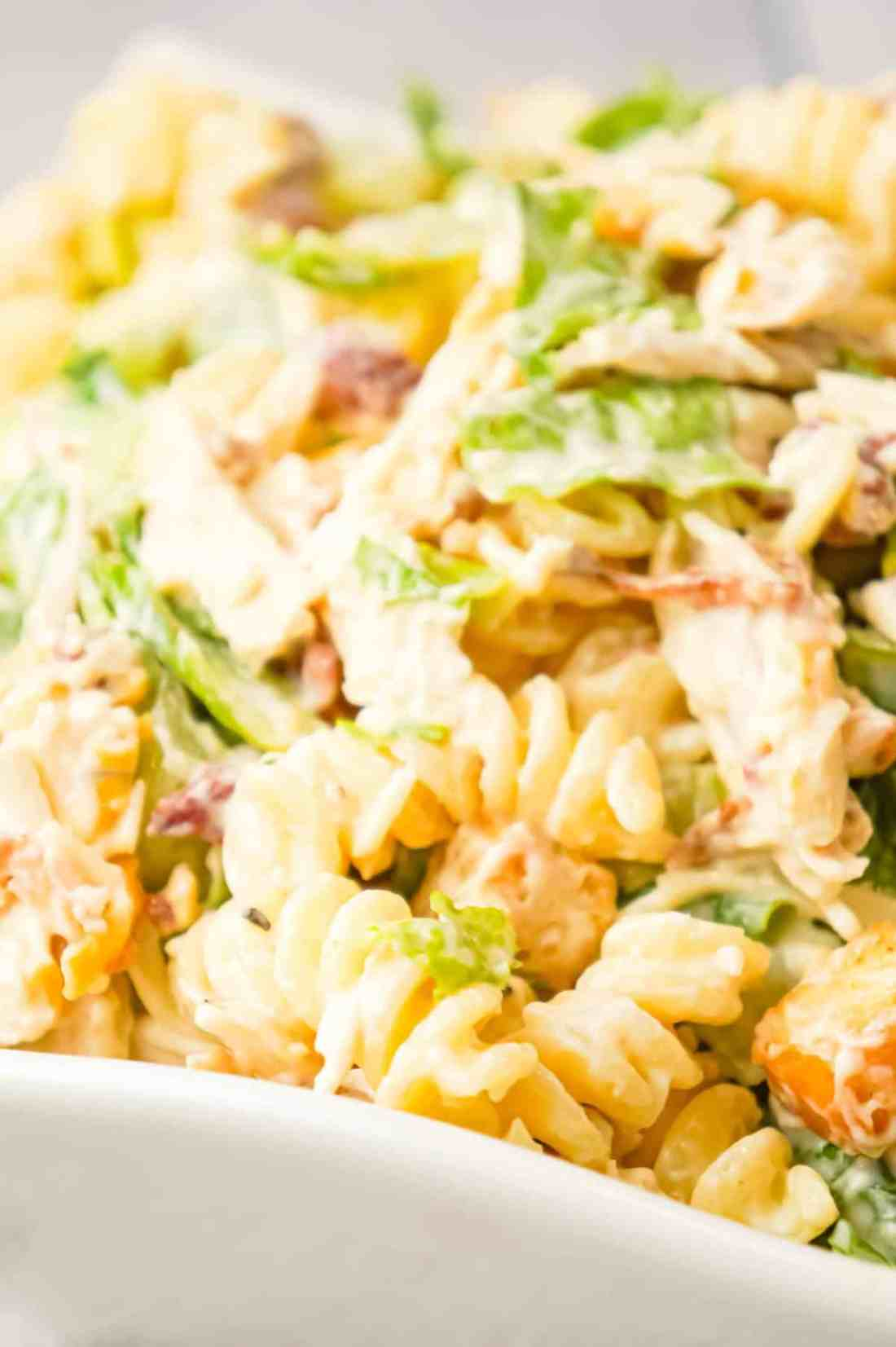 Chicken Caesar Pasta Salad is a tasty side cold dish recipe loaded with chopped romaine, shredded chicken, crumbled bacon, croutons, shredded mozzarella, cheddar and Parmesan cheese all tossed in a creamy garlic Parmesan dressing.