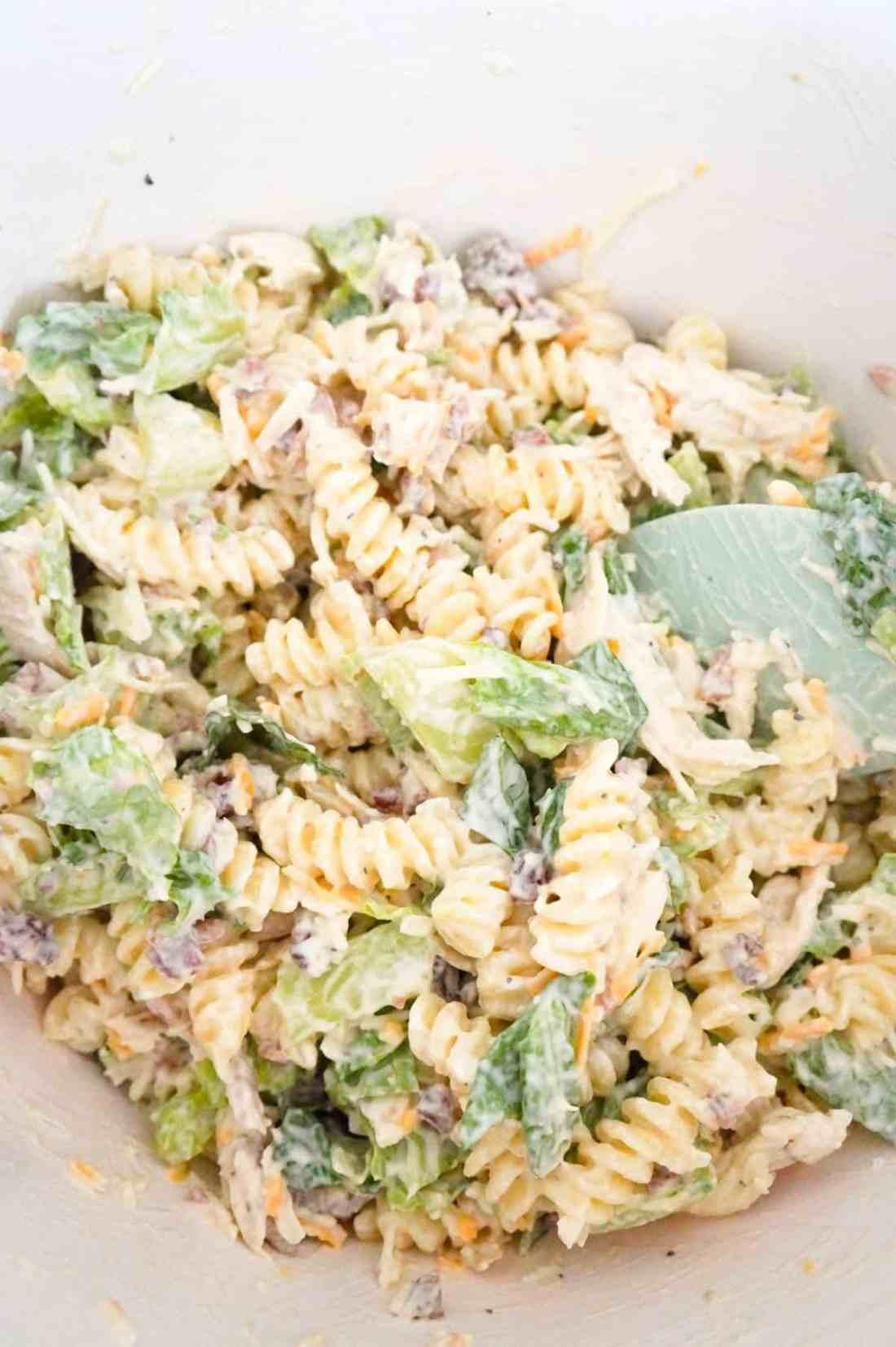 chicken caesar pasta salad mixture in a mixing bowl