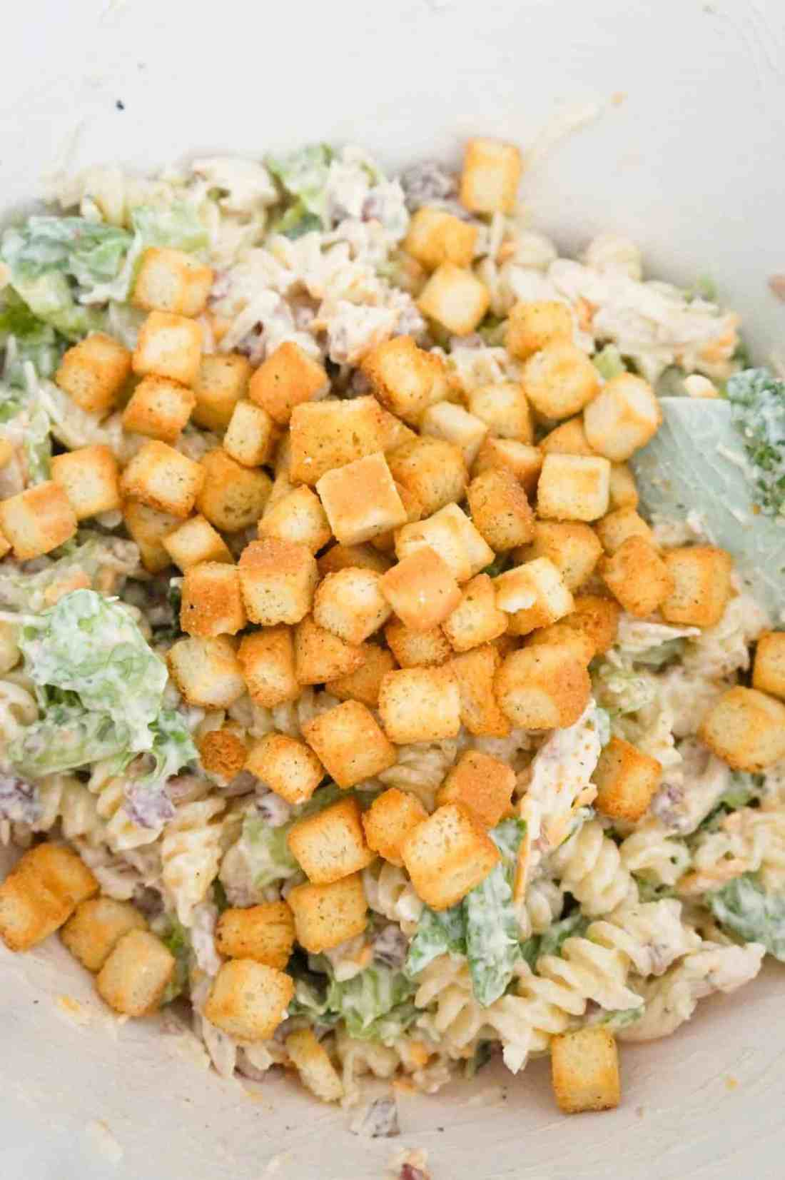 croutons on top of chicken caesar pasta salad in a mixing bowl