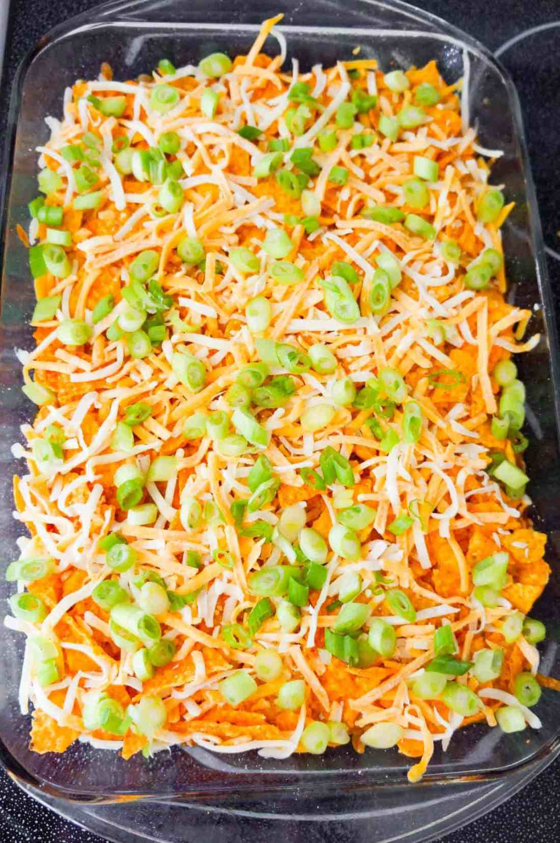 chopped green onions and shredded cheese on top of Doritos Chili Pie