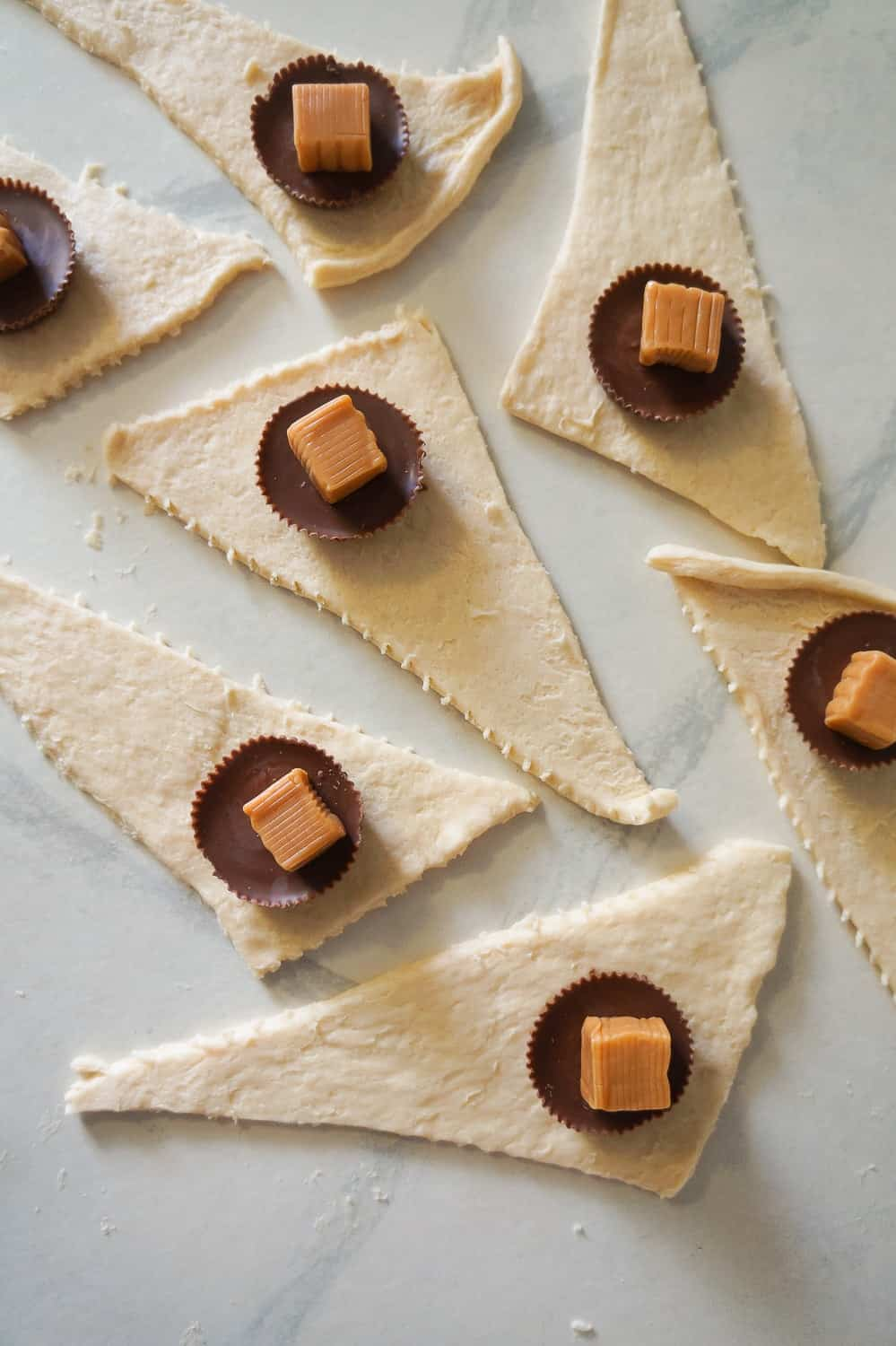 caramels and peanut butter cups on top of triangles of crescent roll dough