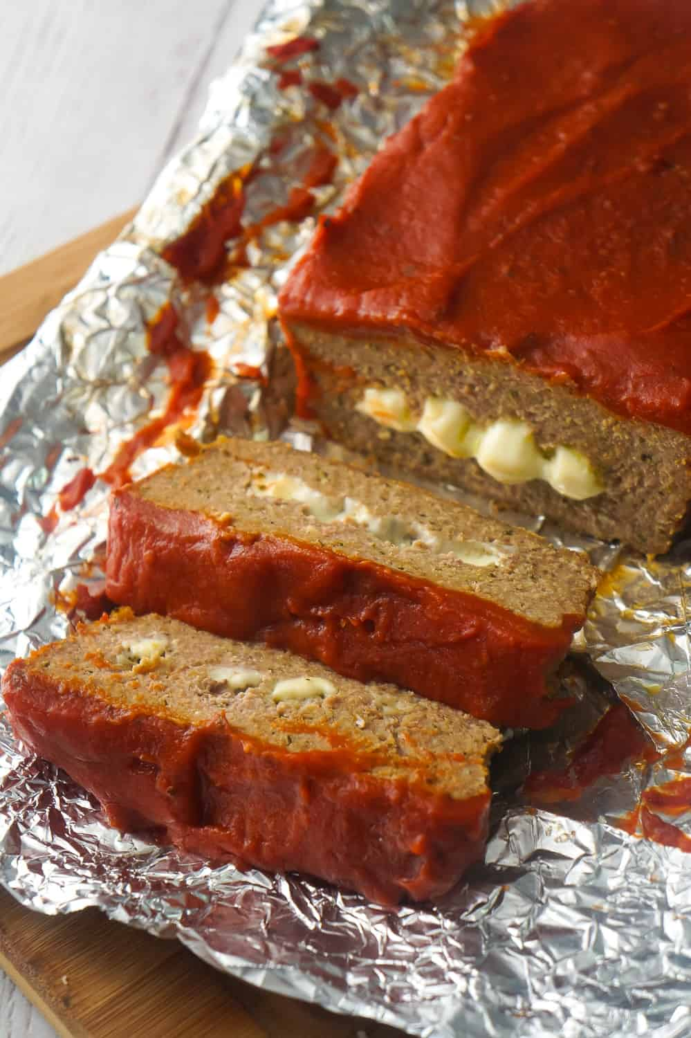 Cheese Stuffed Ground Chicken Meatloaf is an easy dinner recipe loaded with Italian flavours. This chicken meatloaf is made with Italian seasoned bread crumbs, basil pesto, mozzarella cheese and topped with pizza sauce.