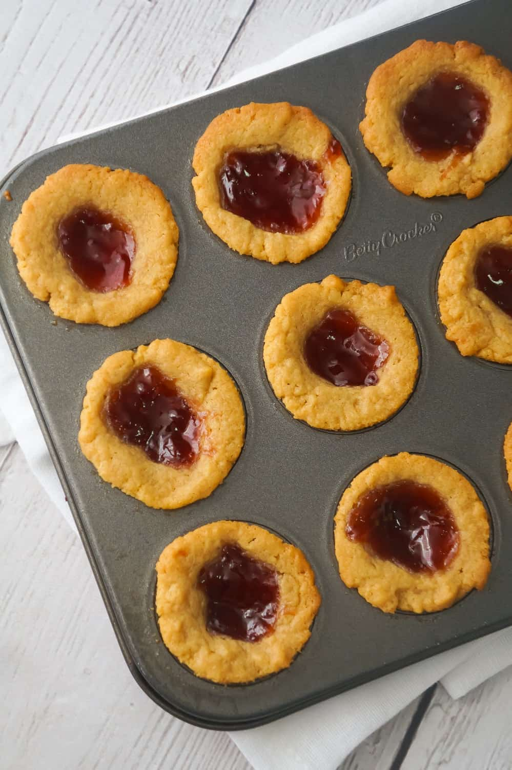 Peanut Butter and Jelly Blondie Bites are a delicious bite sized dessert baked in mini muffin tins. These peanut butter blondies are topped with strawberry jam and baked to perfection.