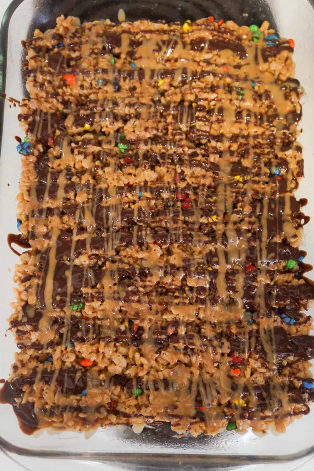 melted peanut butter and chocolate drizzled over rice krispie treats