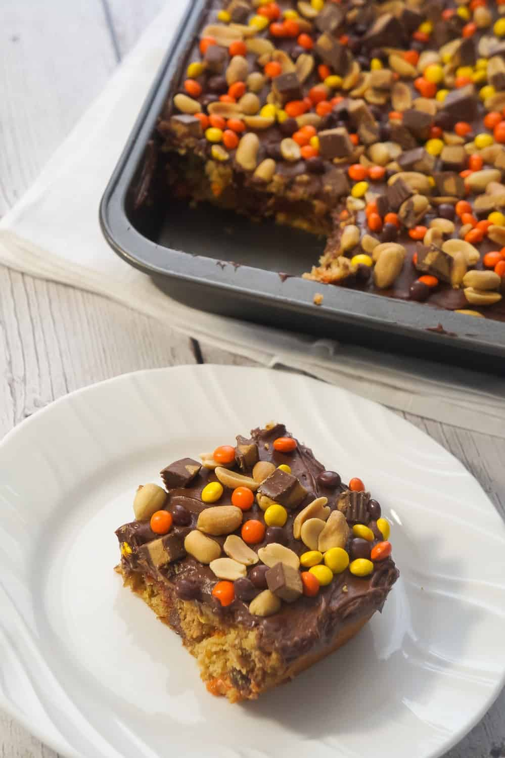 Ultimate Peanut Butter Banana Sheet cake is an easy chocolate peanut butter dessert recipe using boxed cake mix. This delicious cake is topped with chocolate frosting and loaded with peanut butter cups, Reese's Pieces and peanuts.