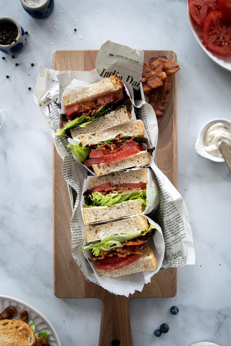 BLT sandwiches on a wood board