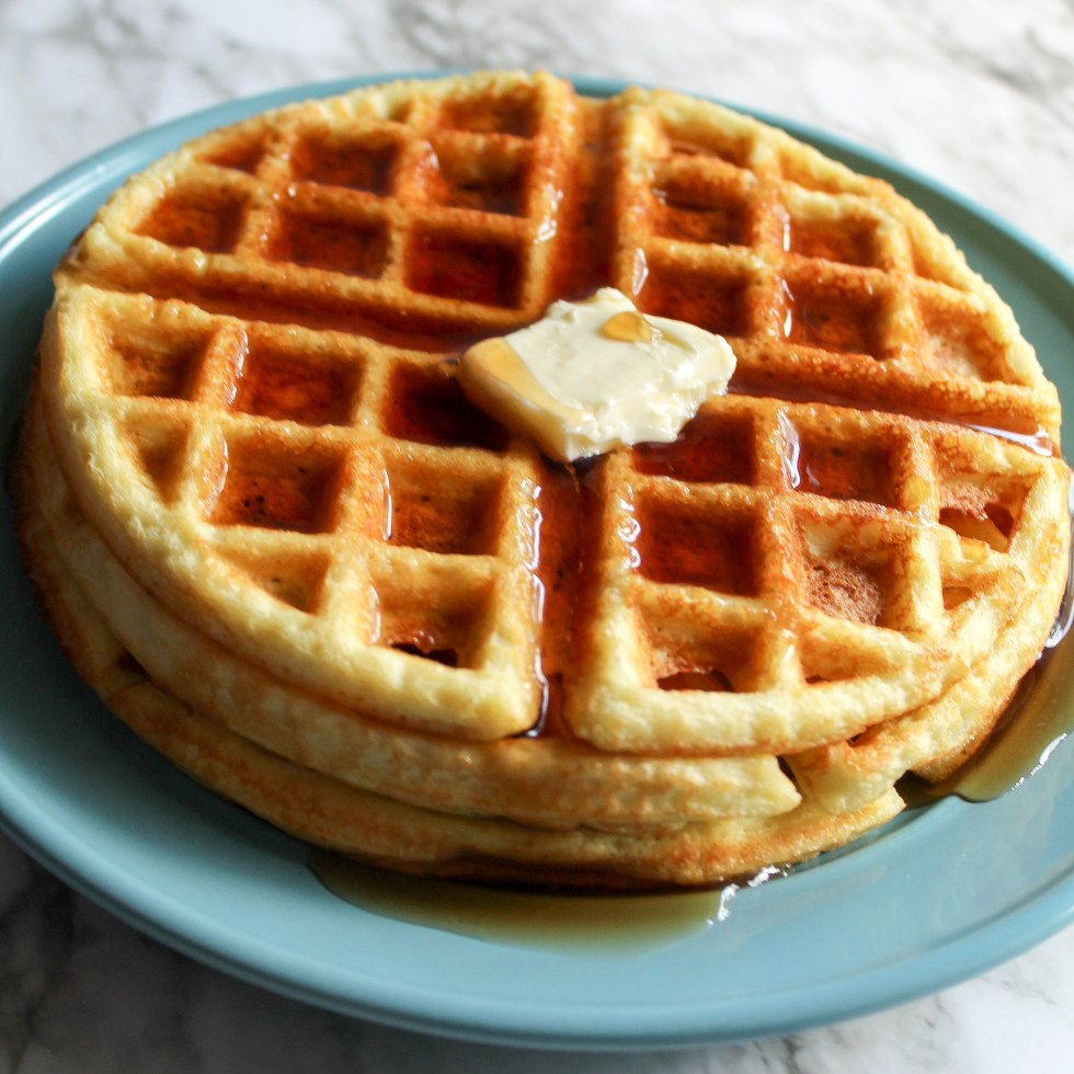overhead shot of keto waffles topped with butter and syrup.