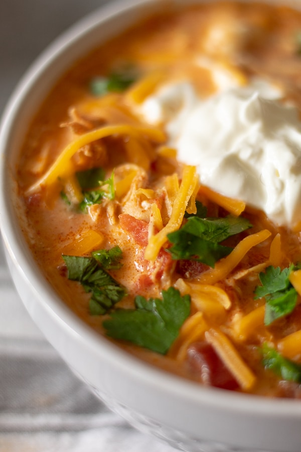 Creamy Chicken taco soup in a white bowl with sour cream