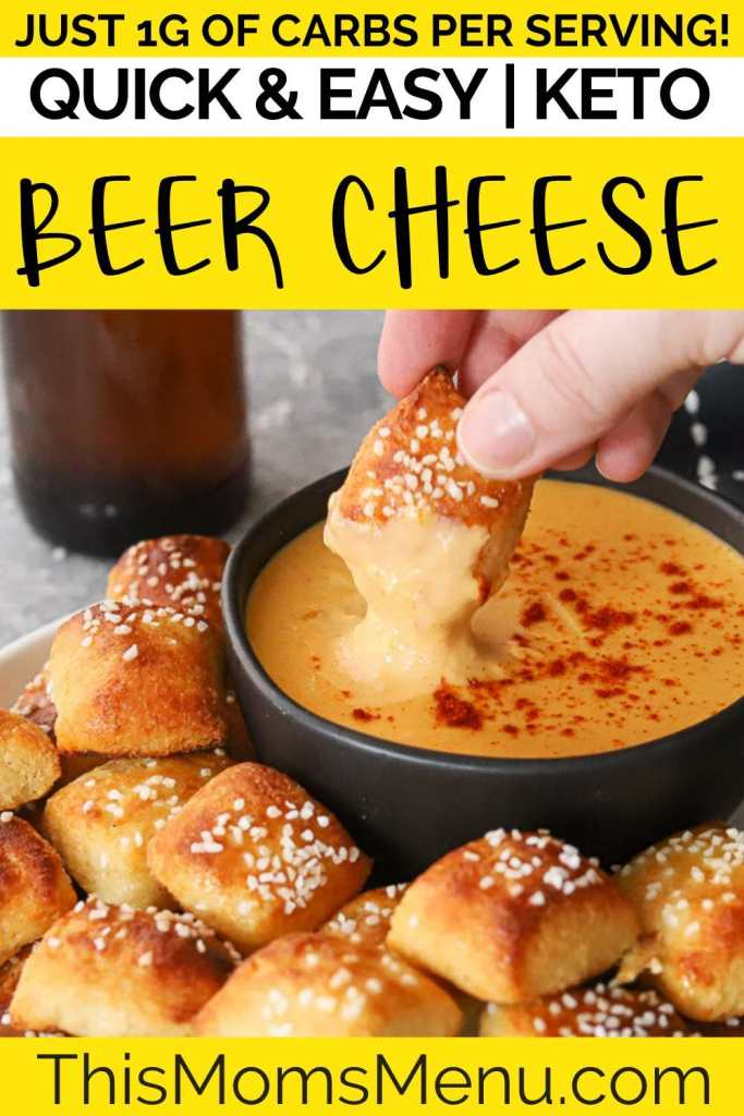 A soft pretzel bite being dunked into beer cheese dip