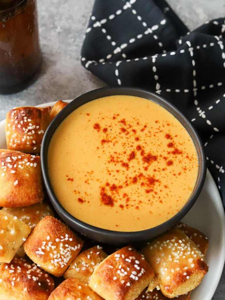 a black bowl full of keto beer cheese  dip surrounded by low carb soft pretzel bites