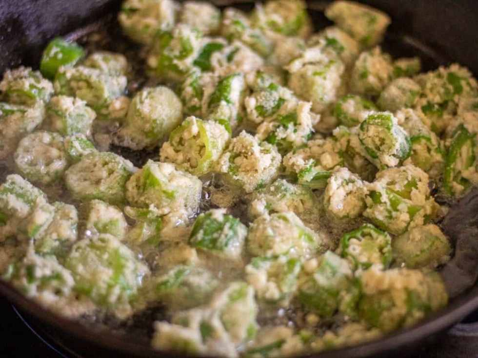 okra being fried in a cast iron skillet