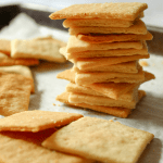 Parchment paper with scattered square crackers and one tall stack of crackers