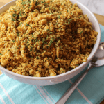 a white bowl full of cauliflower rice pilaf, sitting on top of a blue towel, with a spoon off to the side.