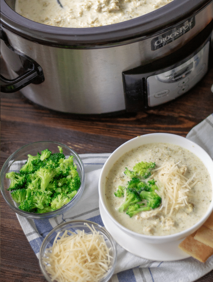 slow cooker chicken broccoli alfredo soup in a white bowl, with steamed broccoli and shredded Parmesan cheese on the side