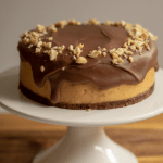Keto chocolate peanut butter cheesecake on white cake stand