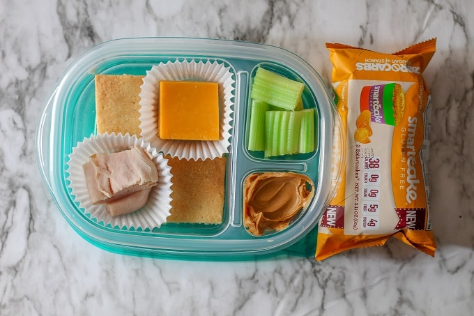 A 3 compartment food storage container with almond crackers, cheddar cheese, turkey and celery with peanut butter, plus a tangerine smart cake.