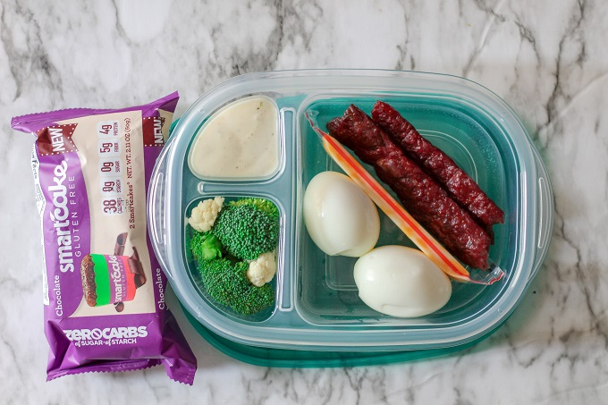 A 3 compartment food storage container with jerky, cheddar cheese, hard boiled eggs, broccoli and ranch, plus a chocolate smart cake.