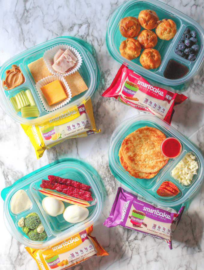 Four divided food storage containers full of various lunch ingredients and 4 packages of smart cakes.