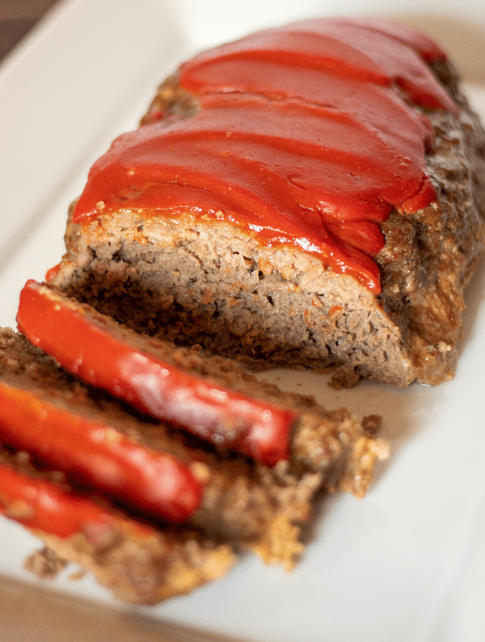 keto southern style meatloaf, topped with ketchup sliced on a white platter