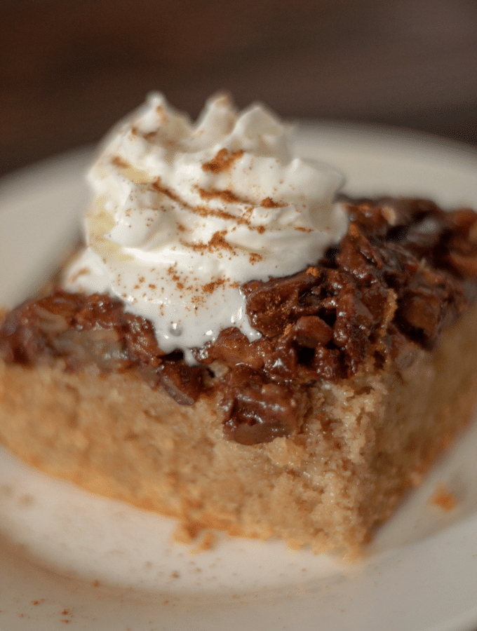 a square slice of upside down maple pecan cake topped with whipped cream, sitting on a round white plate.