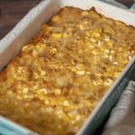 A blue casserole dish full of golden brown keto corn pudding