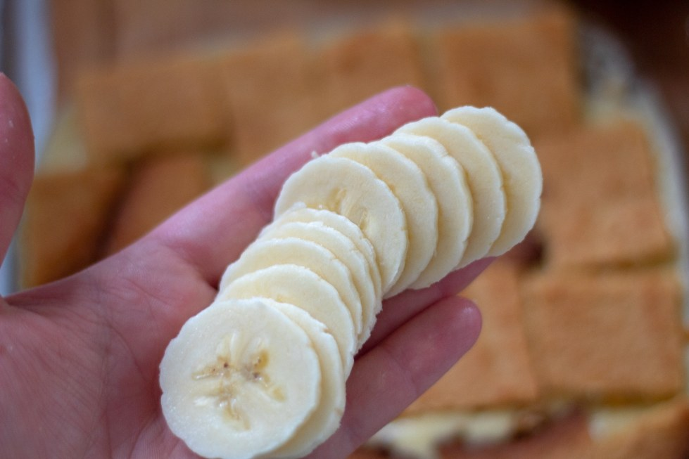 thinly sliced bananas on an outstretched hand preparing for keto banana pudding