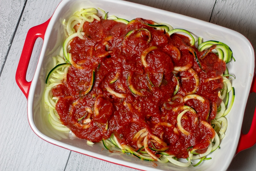 preparation of Keto Chicken Parmesan Casserole with layers of zoodles and marinara