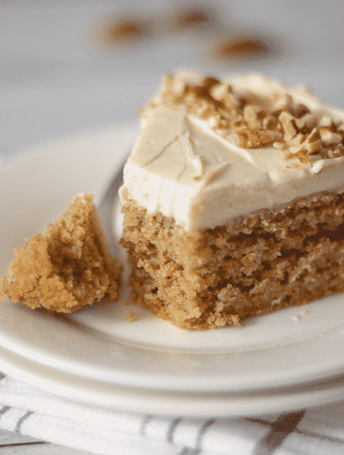 A slice of keto carrot cake with cream cheese frosting on a white plate with one bite taken