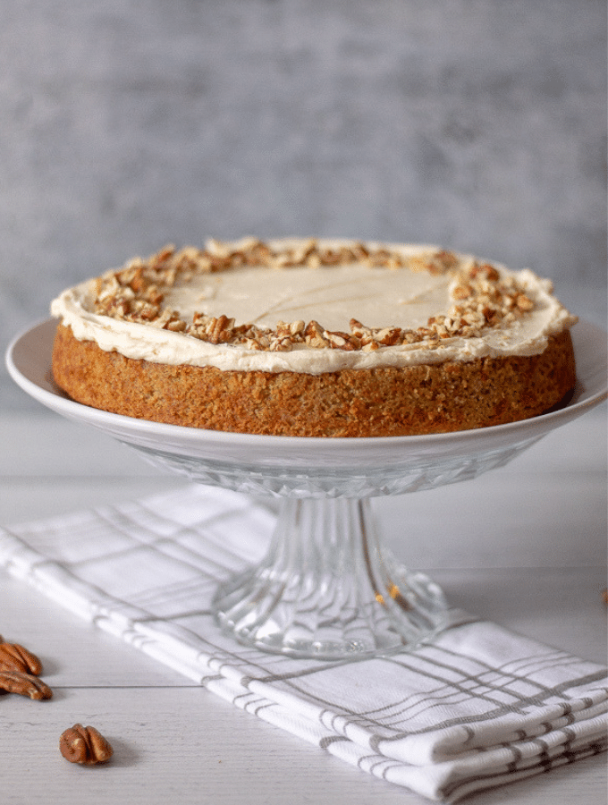 Keto Carrot cake with cream cheese frosting topped with chopped pecans on a glass cake stand