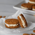 two Keto carrot cake whoopie pies on a piece of parchment with a scattering of pecans and a tray with more .whoopie pies in the backgound